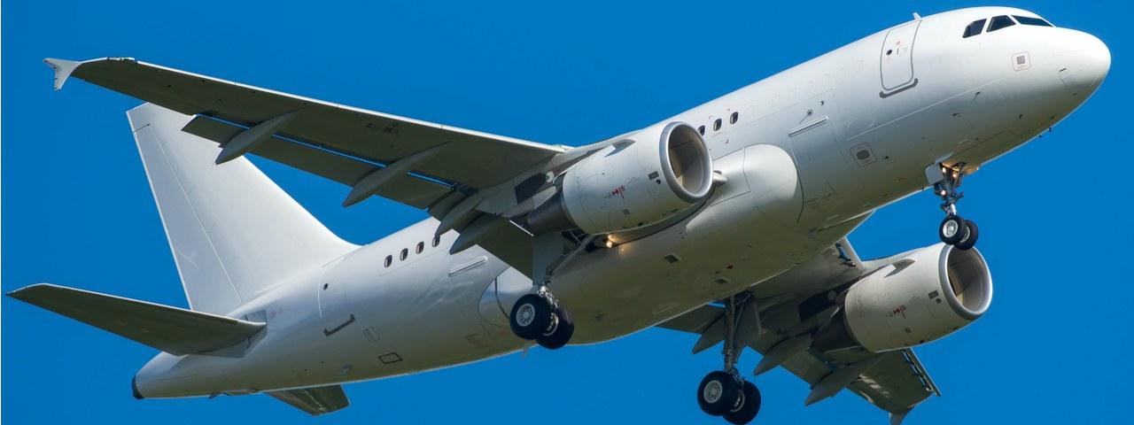 An Airbus A318 in flight against a blue sky
