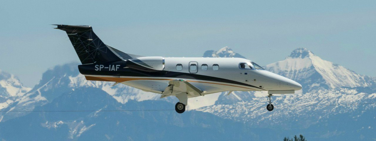 An Embraer Phenom 100 flying past snow-capped mountains